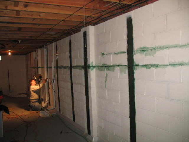 Man installing carbon fiber stabilization in basement